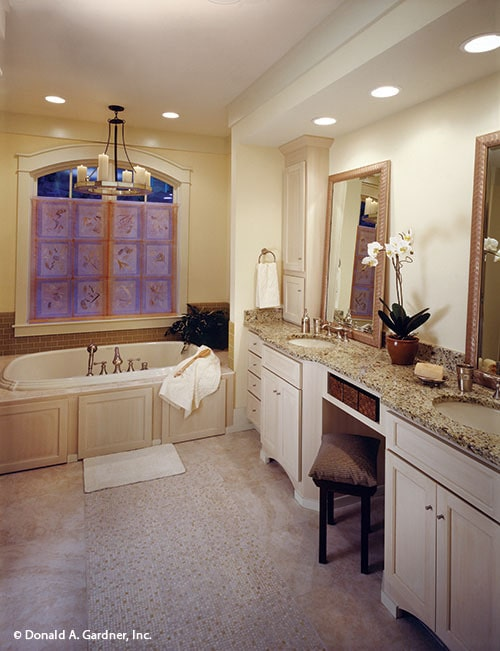 Primary bathroom with a round chandelier, dual sink vanity, and a drop-in bathtub fixed under the arched window.