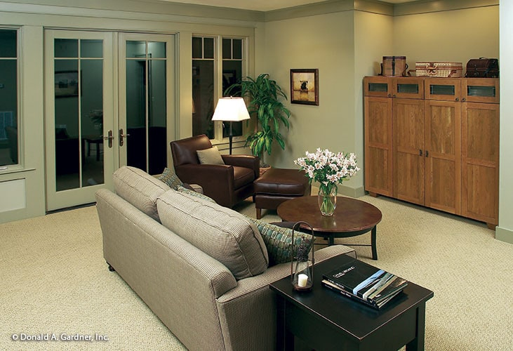 Recreation room with french door, wooden cabinet, leather lounge chair, and a beige sofa.
