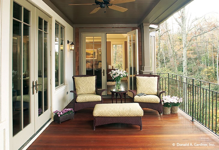 The rear porch is filled with small potted plants, a round side table, cushioned wicker chairs, and a matching ottoman.