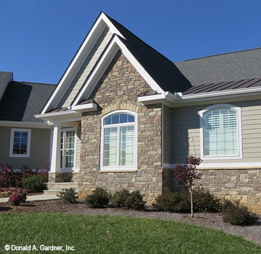 Home facade showing the stone exterior, gable rooflines, and arched windows.