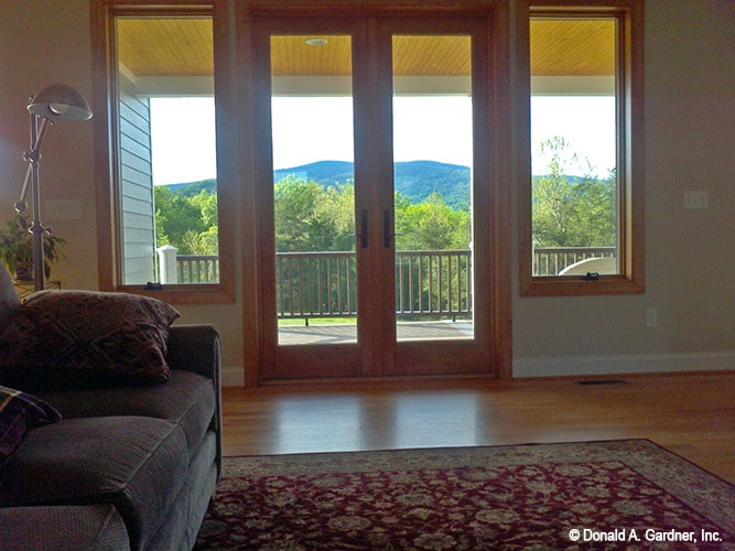 The living room has a gray sectional, red patterned area rug, and a french door that opens out to the rear deck.