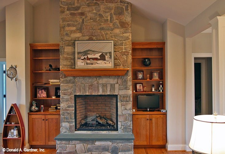 Wooden built-ins flanked the stone fireplace that's topped by a landscape artwork.