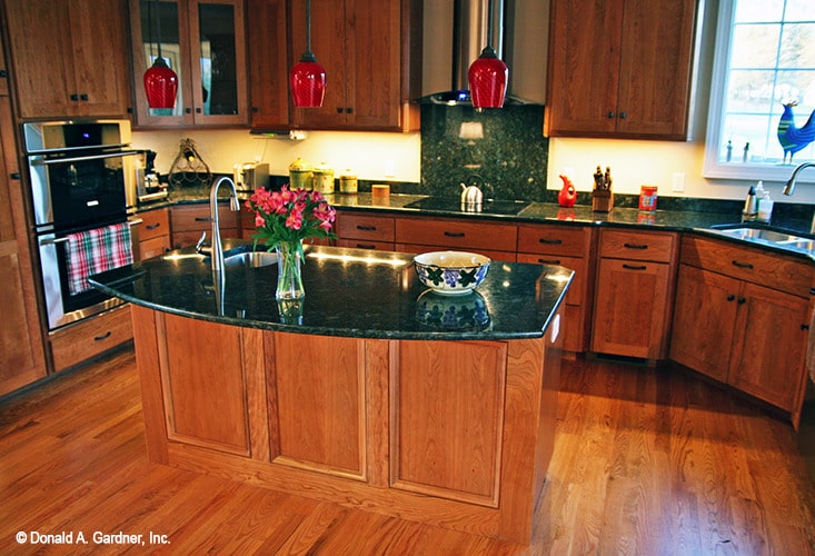 The kitchen is equipped with black granite countertops, stainless steel appliances, undermount sinks, and wooden cabinets.