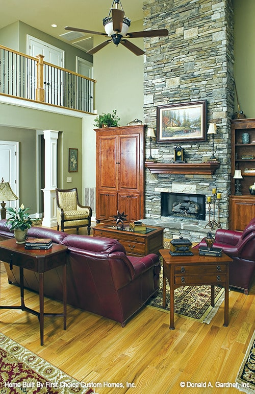 Living room with a stone fireplace, red leather seats, and wooden tables that match the built-in cabinets.