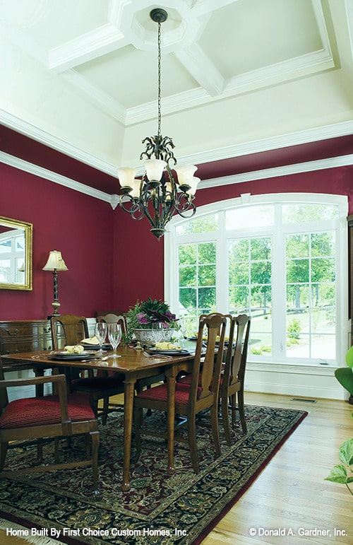 Formal dining room with an arched window, red walls, and a rectangular dining set.