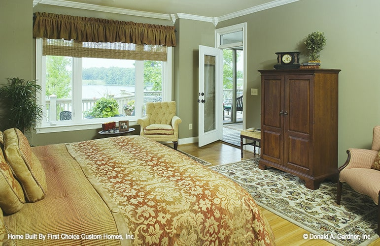 The primary bedroom has a cozy bed, upholstered chairs, a wooden cabinet, and patterned rugs.