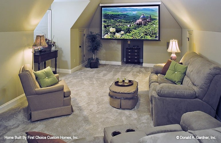 Recreation room with gray seats, skirted ottoman, and a large screen hanging from the vaulted ceiling.