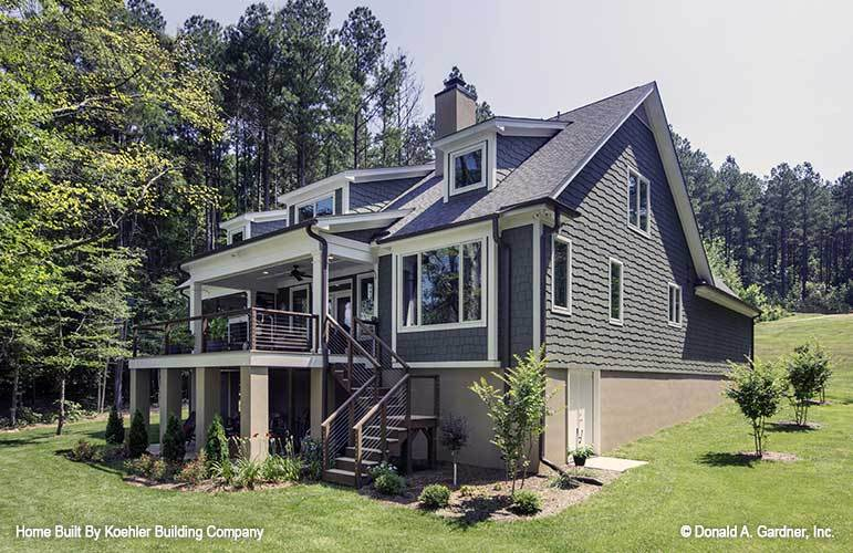 The opposite view shows the cedar shingles, metal staircase, and an expansive sloping lot.