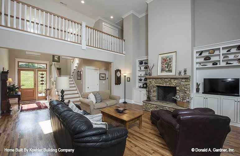 The living room has leather seats, wooden coffee table, and a stone fireplace.