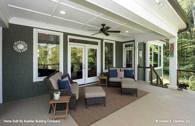 Rear porch filled with wicker seats, matching ottomans, wooden side tables, and a brown area rug.
