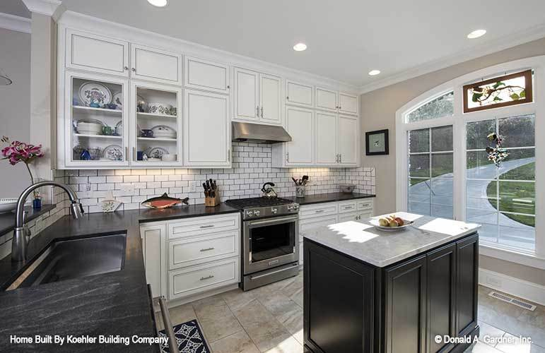 Kitchen equipped with stainless steel appliances, marble countertops, white cabinets, and subway tile backsplash.