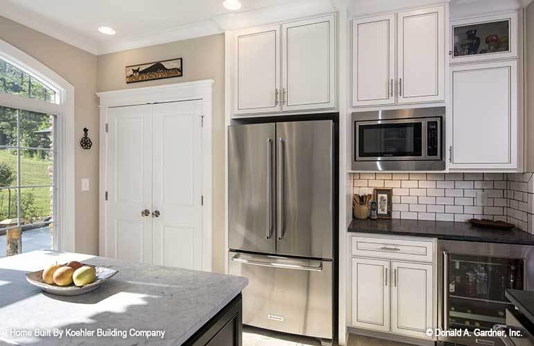 White double door next to the two-door fridge opens to the pantry.