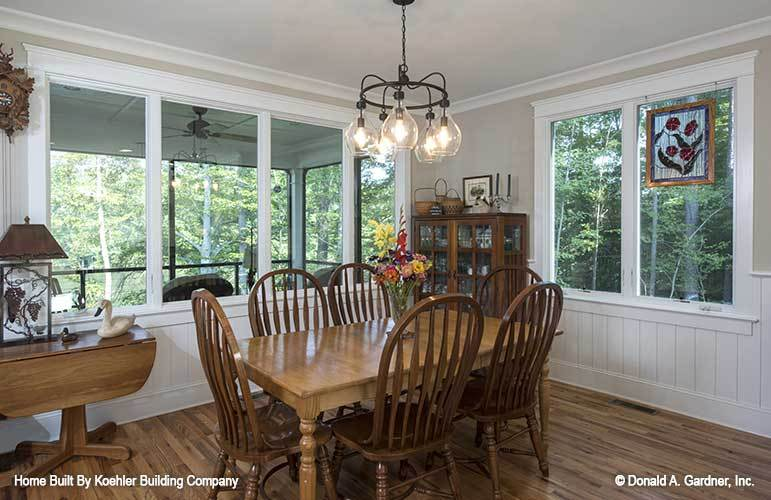The dining room has a wooden console table, round back chairs, and a rectangular dining table well-lit by a glass chandelier.