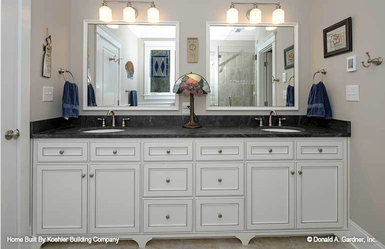 The white vanity has a black marble countertop, two sinks, and a pair of framed mirrors.