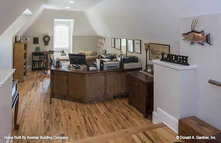 Study with wooden cabinets, built-in desk, hardwood flooring, and a vaulted ceiling fitted with recessed lights.