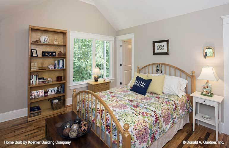 This bedroom has a skirted bed, white nightstand, and a wooden shelving unit that blends in with the hardwood flooring.
