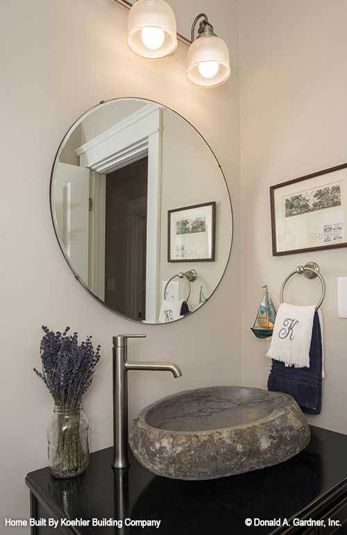 Powder room with a round mirror and a black vanity topped by a stone vessel sink.
