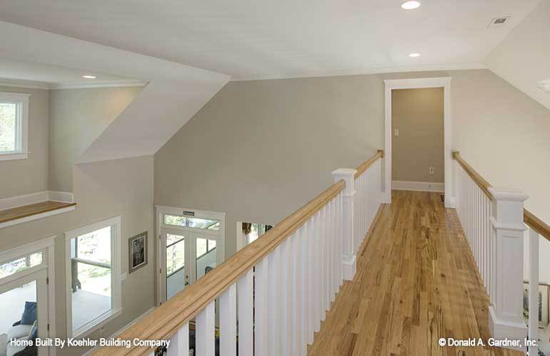 Balcony loft with vaulted ceiling, white railings, and hardwood flooring.