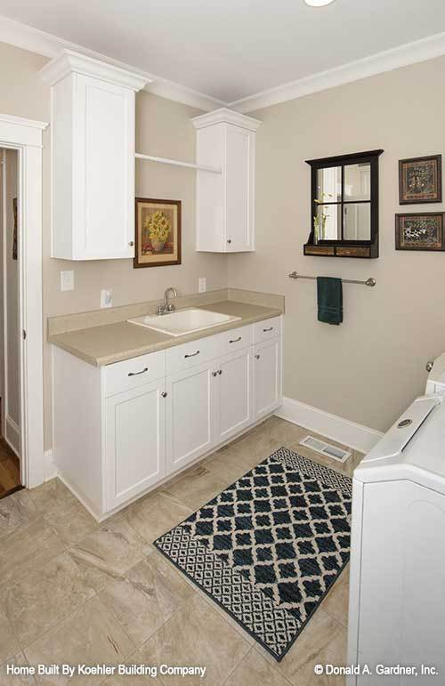 Utility room with custom cabinets, porcelain sink, white appliances, and a black patterned rug that lays on the marble tiled flooring.