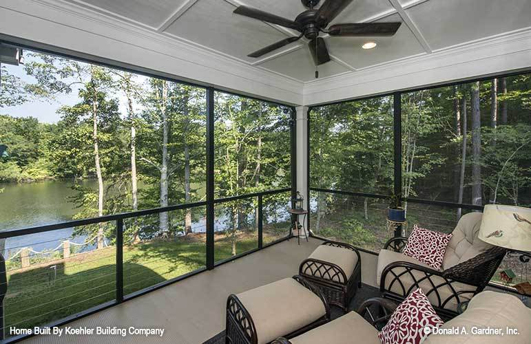 The screened porch has wicker chairs paired with matching ottomans.