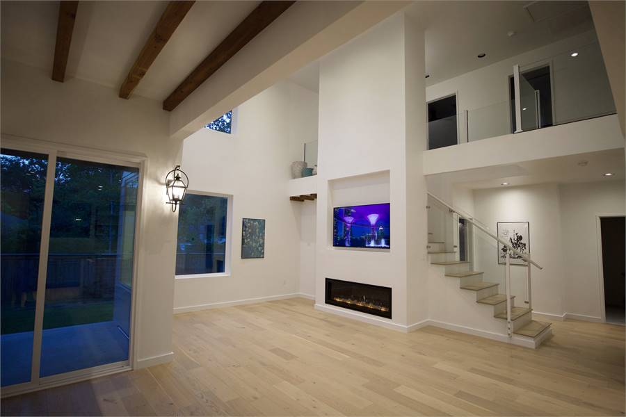 Night view of the living room showcasing the ambient lighting along with tinted glass windows and doors.