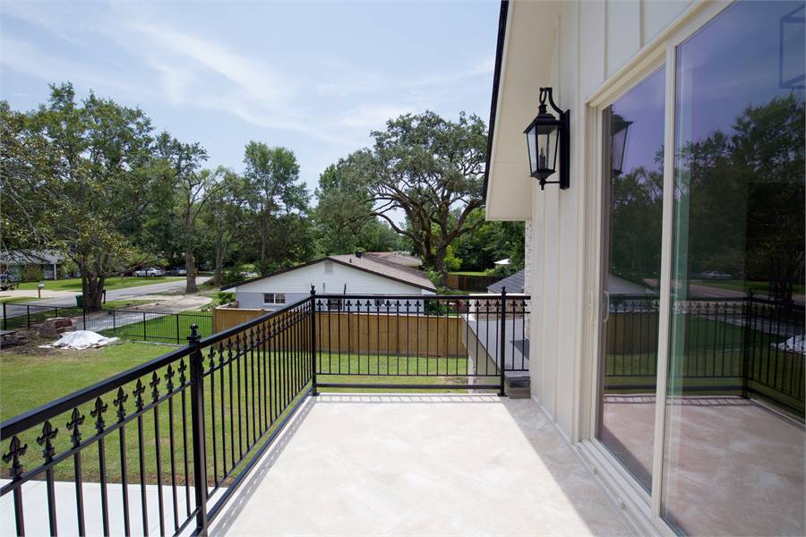 Sliding glass doors open to this balcony framed with ornate wrought iron railings.