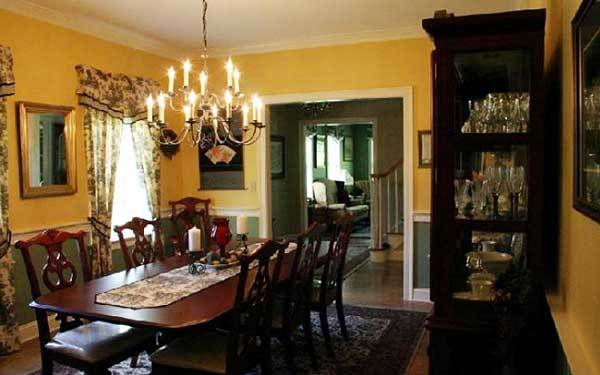 The formal dining room has a display cabinet, cushioned chairs. and a dark wood dining table topped with a printed runner.