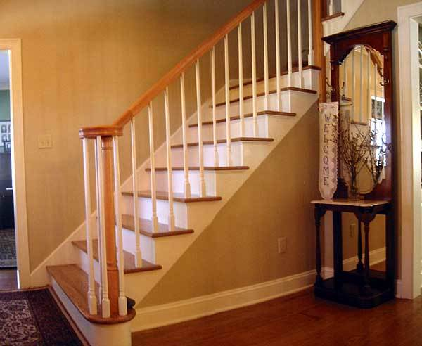 The foyer has a traditional staircase and a wooden console table integrated with a large mirror.