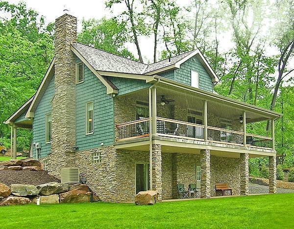 Angled rear view with stone chimney, covered patio, and upper balcony supported by decorative columns.