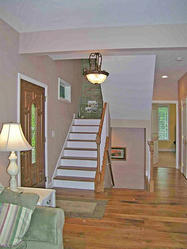 The foyer has a wooden entry door, glass dome chandelier, and a bordered rug that lays on the hardwood flooring.
