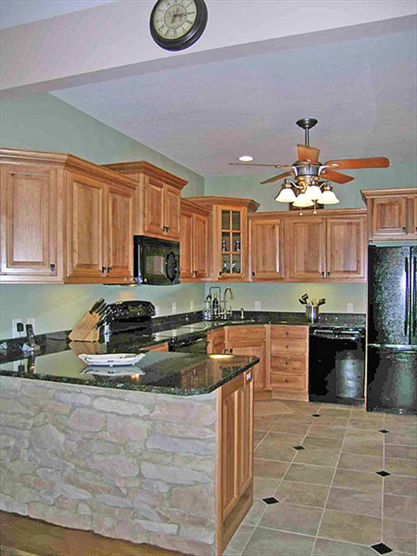 The kitchen is equipped with black appliances, granite countertops, stone peninsula, and wooden cabinets.
