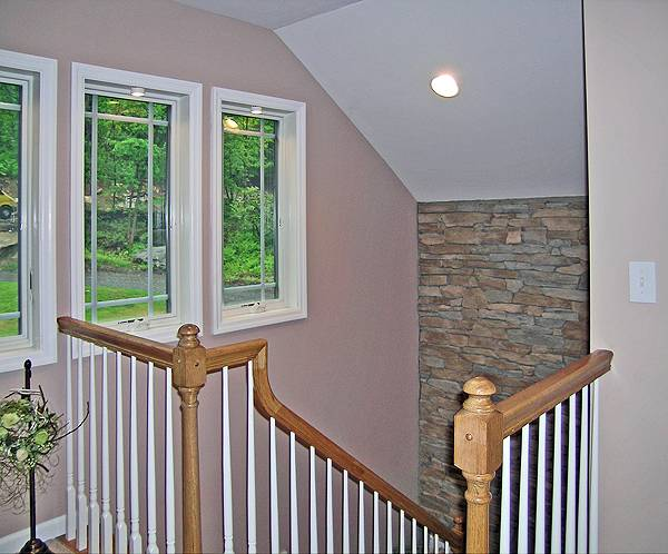 Staircase with wooden handrails and posts leading down the basement.