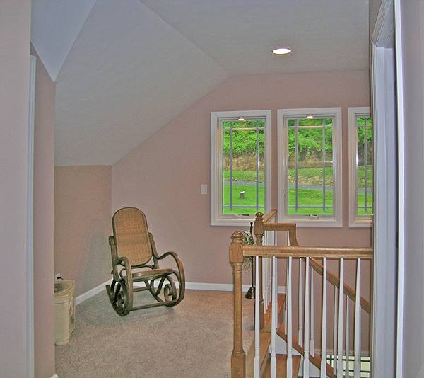 Second-floor landing with vaulted ceiling and rocking chair over beige carpet flooring.