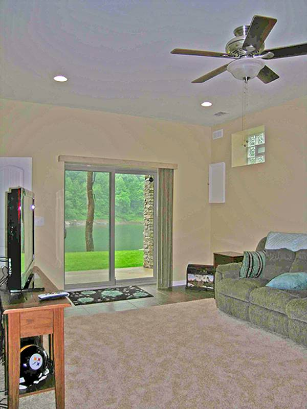 The recreation room has gray sectional, flatscreen TV, and a sliding glass door that opens to the patio.