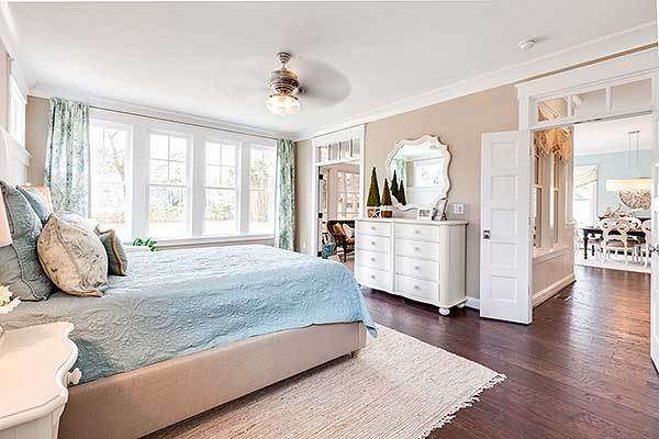 This bedroom has a white dresser, beige upholstered bed, and framed windows that invite natural light in.