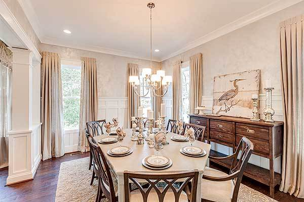 Formal dining room with cushioned chairs, a hexagonal dining table, and a wooden buffet bar.