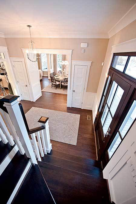 View of the foyer from the staircase showing its glazed front door and a patterned rug that lays on the dark hardwood flooring.