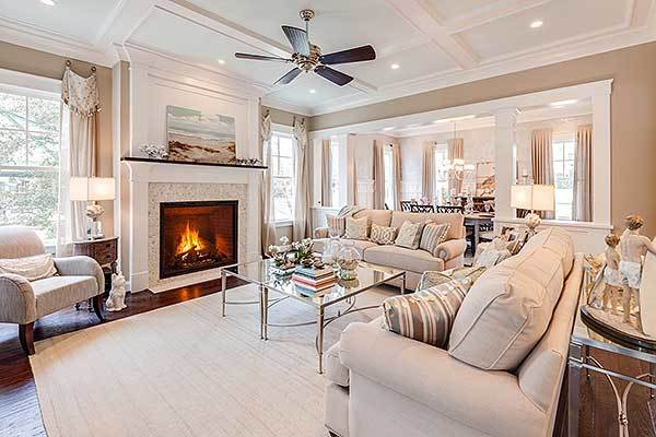 The family room has a coffered ceiling, beige sofas, glass top coffee table, and a warm fireplace.