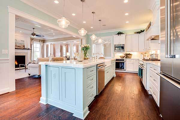 The kitchen is equipped with stainless steel appliances, marble countertops, white cabinets, and a breakfast island.