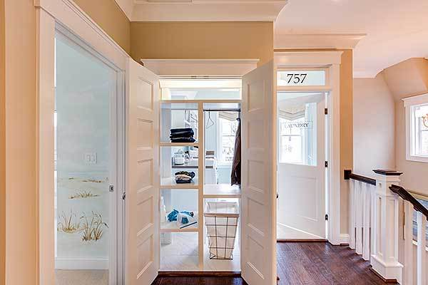 Laundry room with built-in shelves, metal hamper, and white doors.
