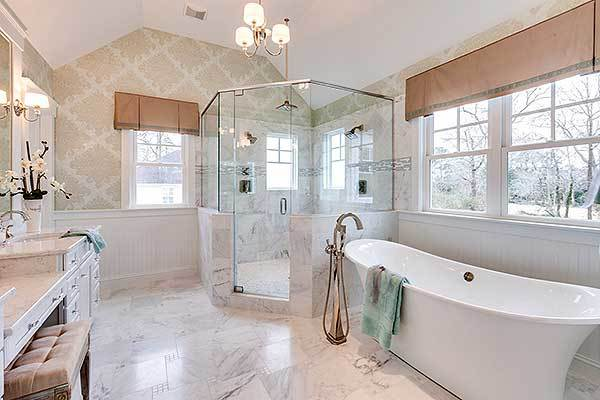 The primary bathroom offers a walk-in shower, a freestanding tub, and a marble top vanity.