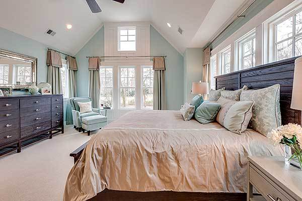Primary bedroom with dark wood furnishings, beige carpet flooring, and a vaulted ceiling.