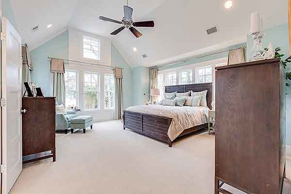 Recessed ceiling lights along with natural light streaming in from the white-framed windows brighten the primary bedroom.