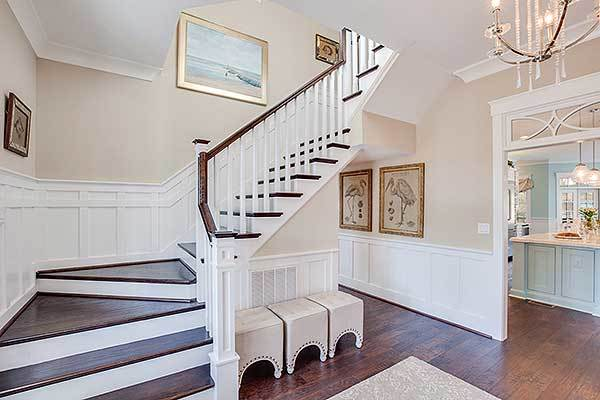 Three contemporary stools are placed under the traditional staircase.