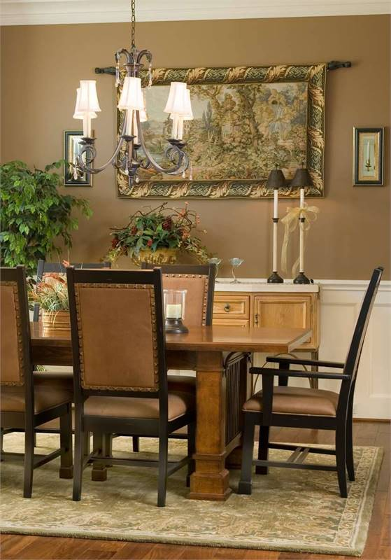 The dining room has an ornate chandelier, rectangular dining set, buffet bar, and brown walls adorned with classic framed artwork and white wainscoting.