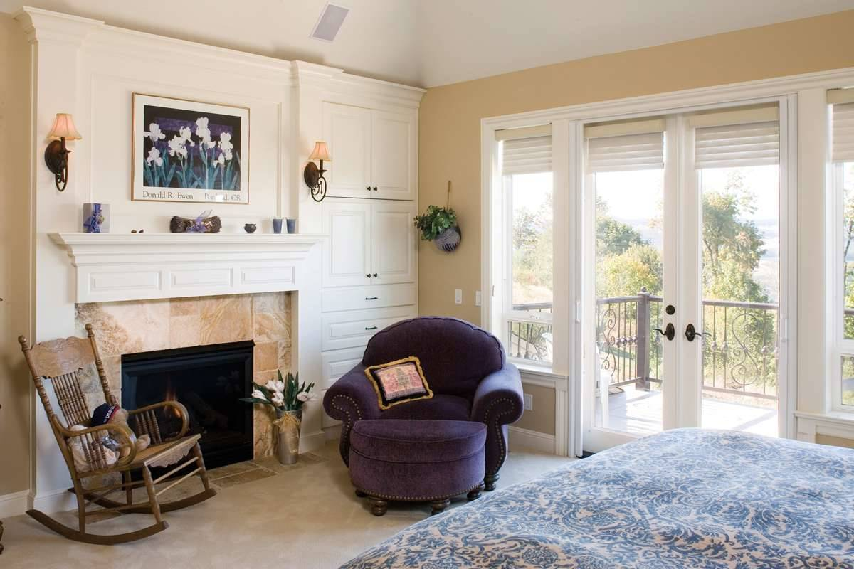 The primary bedroom has a cozy bed, a purple lounge chair, a wooden rocking chair, a fireplace, and a private deck.
