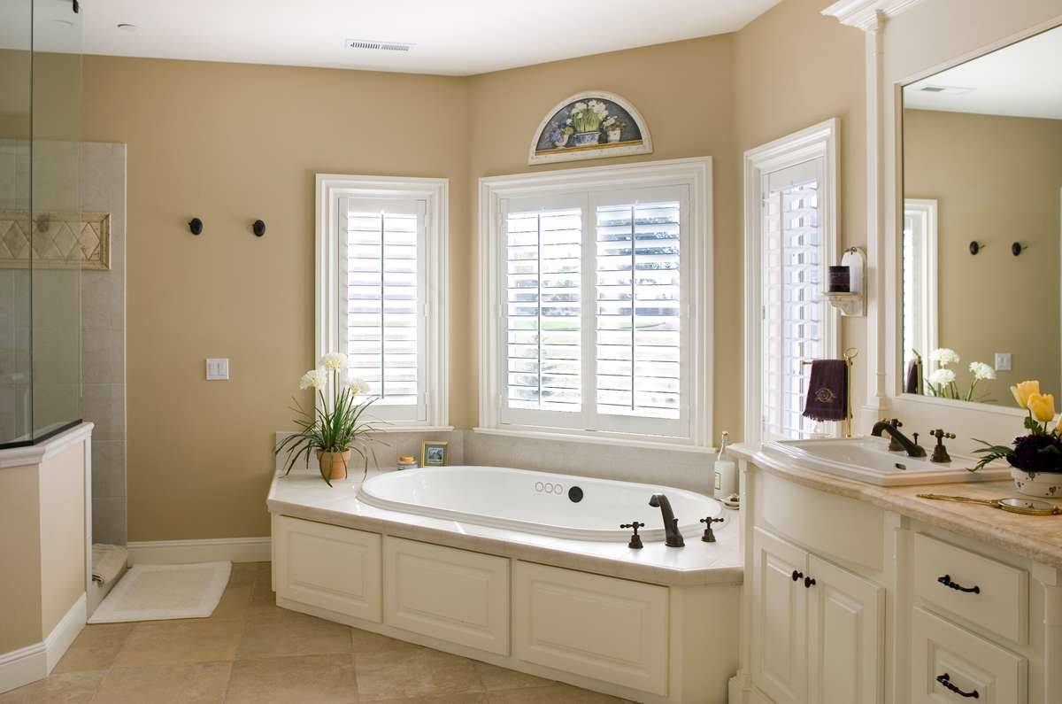 Primary bathroom equipped with a walk-in shower, sink vanity, and a corner tub placed under the bay window.