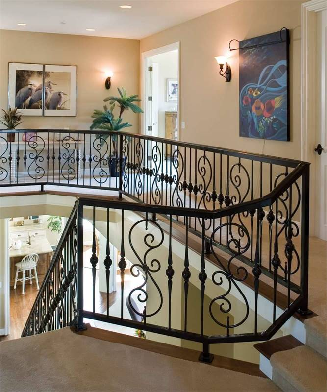 Second-floor balcony with carpet flooring, intricate railings, and beige walls accentuated with lovely artworks.