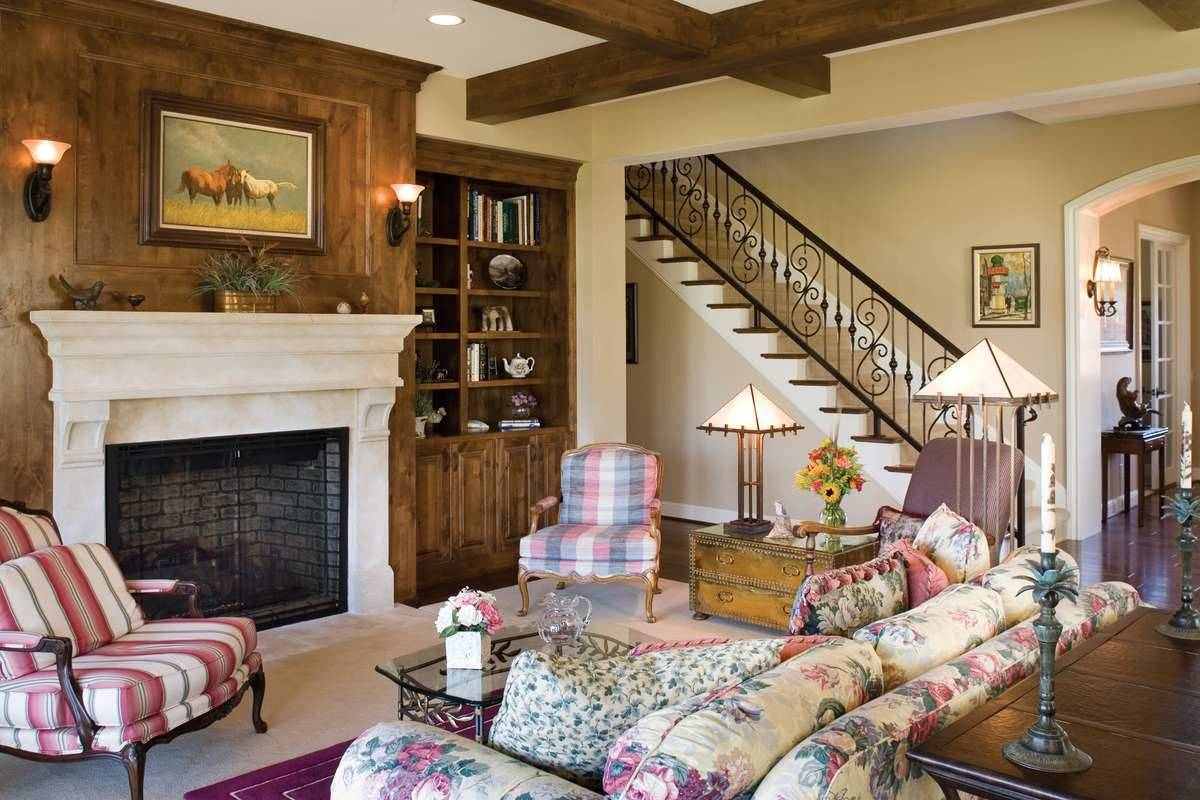 The family room has patterned seats, glass top coffee table, and a fireplace fitted on the wood-paneled wall.