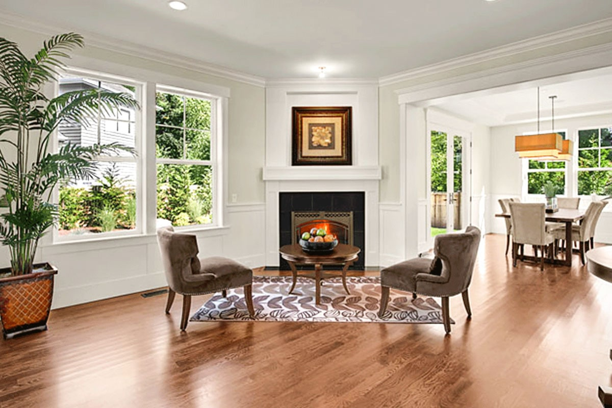 The living room has brown velvet chairs, a round coffee table, and a glass-enclosed fireplace.